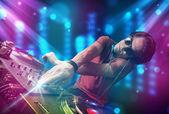 Dj mistura de música em um clube com luzes azuis e roxas — Foto Stock