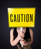 Young woman holding a caution sign — Stock Photo