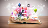 Open book with flying 3d letters on concrete background — Stock Photo