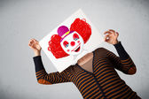 Woman holding a cardboard with a clown on it in front of her hea — Stock Photo