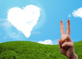 Happy smiley fingers looking at heart shaped cloud — Stock Photo