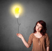 Woman holding a lightbulb balloon — Stock Photo