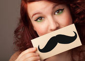 Happy cute girl holding paper with mustache drawing — Stock Photo