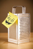 Post-it note with smiley face sticked on a grater — Stock Photo