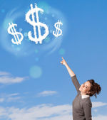 Young girl pointing at dollar sign clouds on blue sky — Stock Photo