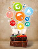 Suitcase with colorful summer icons and symbols — Stock Photo