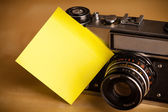 Empty post-it note sticked on photo camera — Stock Photo