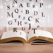 Opened book with flying letters — Stock Photo