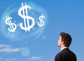 Businesman pointing at dollar sign clouds on blue sky — Stock Photo