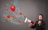 Mladý kluk baví, křičel do megafonu s balónky — Stock fotografie