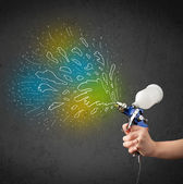Worker with airbrush gun paints colorful lines and splashes — Stock Photo