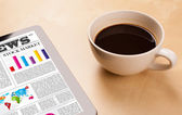 Tablet pc shows news on screen with a cup of coffee on a desk — Stock Photo