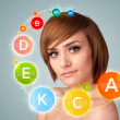 Pretty young girl with colorful vitamin icons and symbols — ストック写真