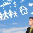 Businessman daydreaming with family and household clouds — Stock Photo #30738895