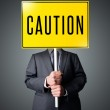 Businessman holding a caution sign — Stock Photo #30739239