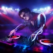 Disc jockey playing music with light beam effects on stage — Foto de Stock
