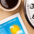 Stock Photo: tablet pc showing weather forecast on screen with a cup of coffe