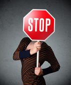 Young woman holding a stop sign — Stock Photo