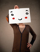 Woman holding a cardboard with a smiley face on it — Stock Photo