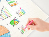Business person drawing colorful graphs and icons on paper — Stock Photo