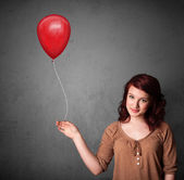 Woman holding a red balloon — Stock Photo