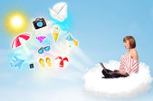 Young businessman sitting in cloud with laptop — Stock Photo