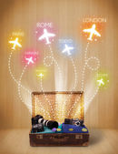 Travel bag with clothes and colorful planes flying out — Stock Photo
