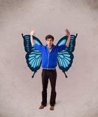 Joven guapo con ilustración mariposa azul en la parte posterior — Foto de Stock