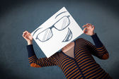 Woman holding a paper with smiley face in front of her head — Stock Photo
