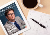 Tablet pc showing magazine on screen with a cup of coffee on a d — Stock Photo