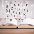 Opened book with flying letters — Stockfoto