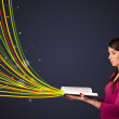 Pretty young woman reading a book while colorful lines are comin — Stock Photo