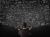 Businessman standing in front of drawn charts on a blackboard — Stock Photo