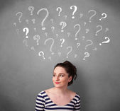 Young woman with question marks above her head — Foto Stock