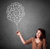 Vrouw met een bos van glimlachen ballonnen — Stockfoto