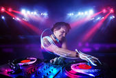 Disc jockey playing music with light beam effects on stage — Stock Photo