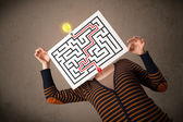 Woman holding a paper with a labyrinth on it in front of her hea — Stock Photo