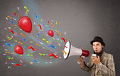 Young guy having fun, shouting into megaphone with balloons — 图库照片
