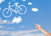 Hand pointing at bicycle clouds on blue sky — Stock Photo