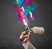 Worker with airbrush and colorful abstract clouds and balloons — Stock Photo