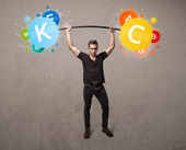 Muscular man lifting colorful vitamin weights — Stock Photo