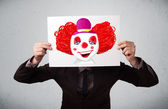 Businessman holding a cardboard with a clown on it in front of h — Стоковое фото