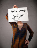 Woman holding a paper with cute smiley face on it in front of he — Stock Photo