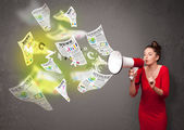 Girl yelling into loudspeaker and newspapers fly out — Stockfoto