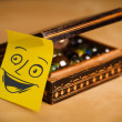 Post-it note with smiley face sticked on a jewelry box — Stock Photo