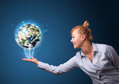 Businesswoman holding glowing earth globe — Stock Photo