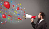 Cara jovem, se divertindo, gritando no megafone com balões — Foto Stock