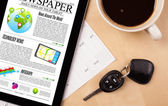 Tablet pc shows news on screen with a cup of coffee on a desk — Stock fotografie
