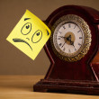 Post-it note with smiley face sticked on clock — 图库照片