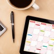 Tablet pc showing calendar on screen with a cup of coffee on a d — Stock Photo #33313591